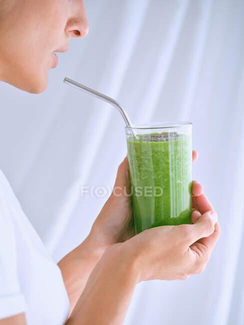 Persona sosteniendo vaso de batido verde - foto de stock