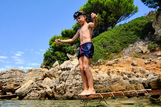 Low angle of wet child in swimming shorts and diving mask looking at surface of water and preparing to jump into sea — Stock Photo
