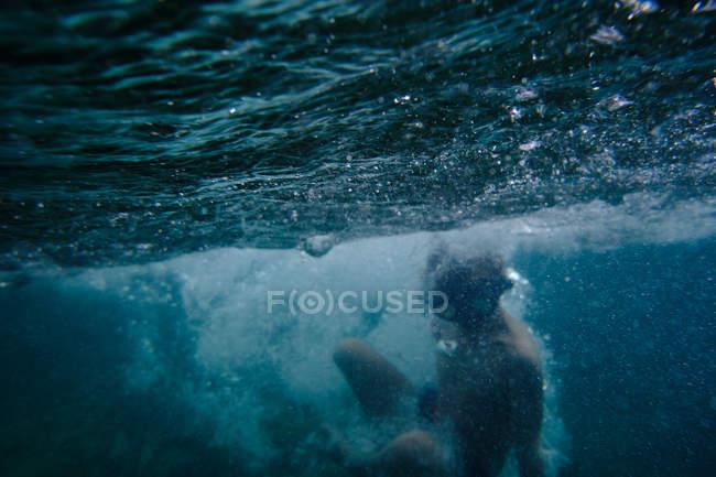 Boy floating among sea waves — Stock Photo