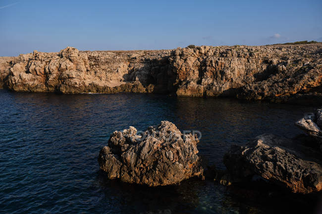 Beautiful and picturesque view of rippled surface of sea water among high rocky cliffs on sunny day — стокове фото