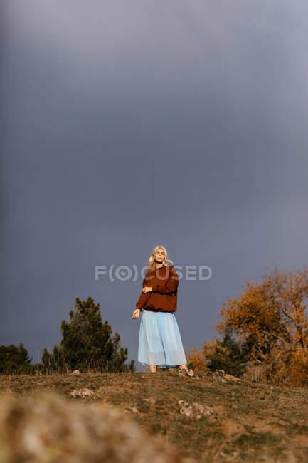 Bella bionda che cammina lungo la campagna autunnale — Foto stock