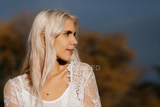 Zärtliche Frau mit weißblonden Haaren beim Betrachten ländlicher Gegenden mit orangefarbenem Laub — Stockfoto