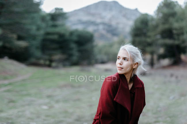 Attractive woman in bright coat walking along evergreen forest — Stock Photo