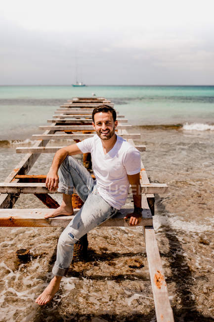 Homme riant en tenue décontractée reposant sur une jetée âgée en été et regardant la caméra — Photo de stock
