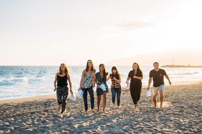 Eine Gruppe junger Leute am Strand rennt in die Kamera, während sie Papiere in der Hand hält — Stockfoto