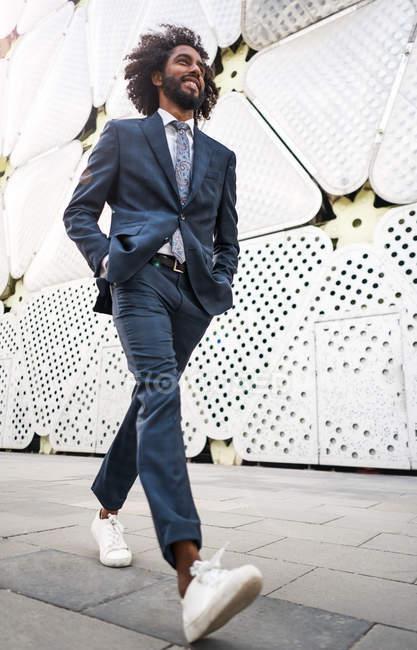 African american office worker walking near modern building — Stock Photo