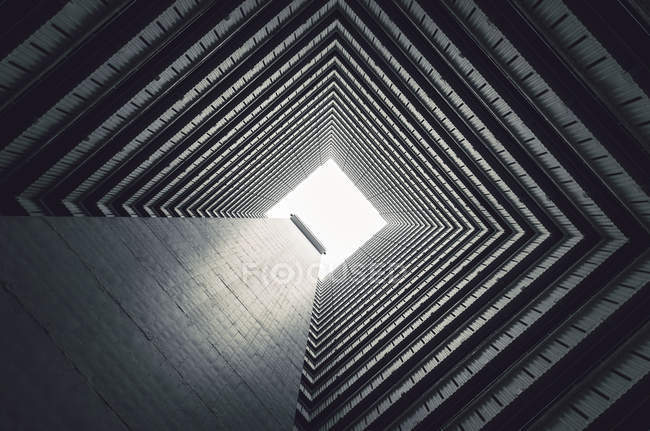 From below of dark inner tunnel of high rise building with gloomy dark facade walls running up — Stock Photo