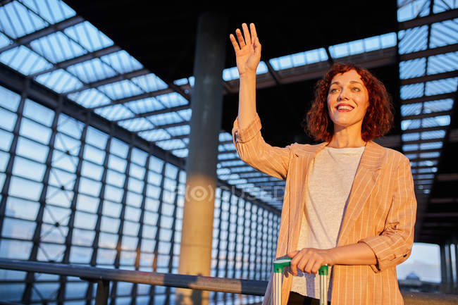 Hübsche lächelnde junge Frau mit Koffer winkt zum Abschied am Bahnhof — Stockfoto