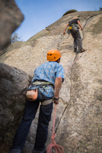 Adventurers climbing mountain wearing safety harness against picturesque landscape — Stock Photo