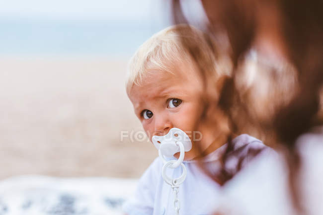 Blond baby with pacifier on the beach — Foto stock