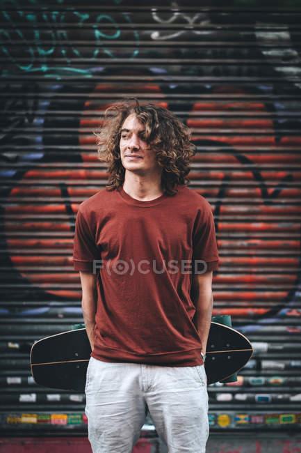 Hombre de confianza con ropa casual portador de palangre a la espalda mientras se encuentra al lado de un edificio moderno. - foto de stock