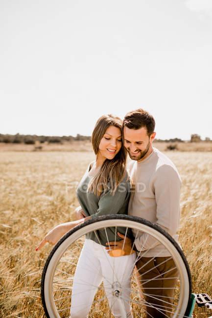 Verliebte posieren mit dem Fahrrad auf Roggenfeld — Stockfoto