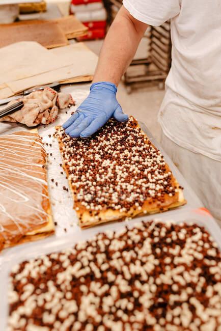 Неузнаваемый кондитер в перчатках, украшающий вкусный свежий торт шоколадной крошкой во время работы на пекарне — стоковое фото