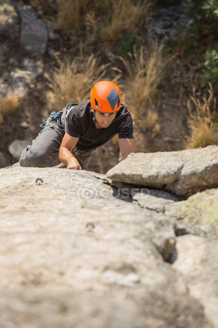 From above man climbing a rock in nature with climbing equipment - foto de stock