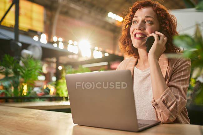 Молодая женщина разговаривает по телефону во время работы на ноутбуке — стоковое фото