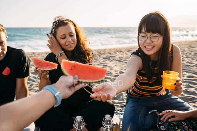 Mujer sonriente le da un trozo de sandía a su amiga con su amiga que bebe jugo de naranja en la playa - foto de stock