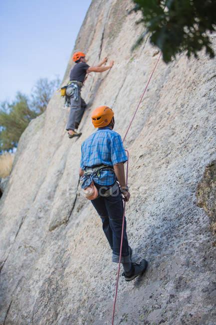 Adventurers climbing mountain wearing safety harness against picturesque landscape - foto de stock