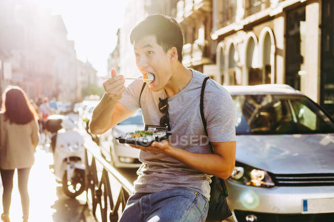 Handsome asian man eating takeaway food while standing by food truck on sunny street — Stock Photo