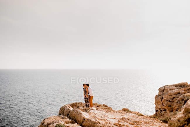 Coppia abbracci su roccia — Foto stock