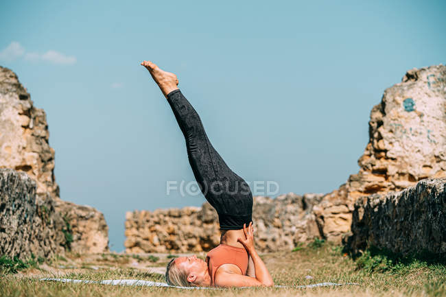 Flexible Frau dehnt sich und praktiziert Yoga in sonniger Landschaft — Stockfoto
