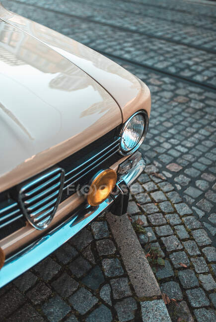 From above shiny beige hood of old vintage car with headlight parked on cobblestone pavement — Stock Photo