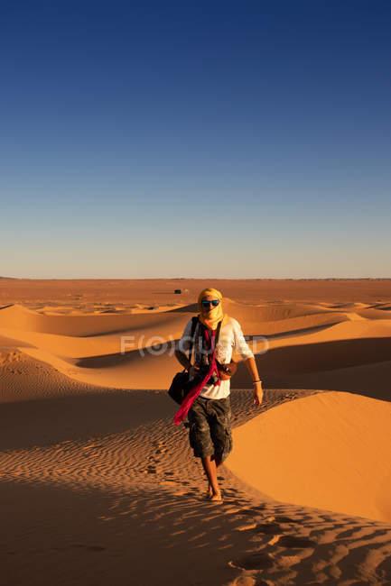 Touriste méconnaissable, les bras tendus, face à un ciel ensoleillé et ensoleillé dans le désert — Photo de stock
