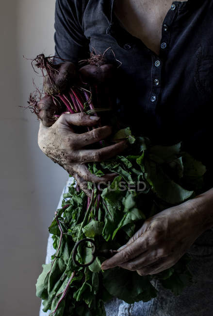 Unrecognizable woman holding bunch of ripe beetroots and vintage key in hands — Stock Photo