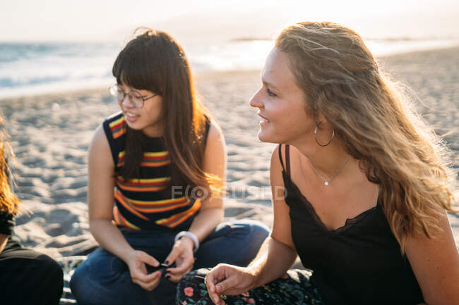 Ein schönes blondes Mädchen plaudert am Strand neben ihrem asiatischen Freund mit einer Gruppe von Freunden — Stockfoto