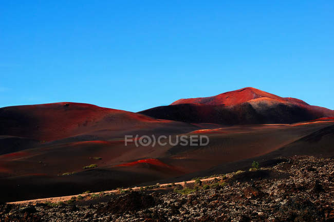 Picturesque view of volcanic terrain with solidified lava in wild area on island of Lanzarote Spain — Stock Photo