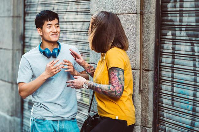 Друзья-представители разных национальностей разговаривают и жестикулируют, стоя рядом с городской застройкой — стоковое фото