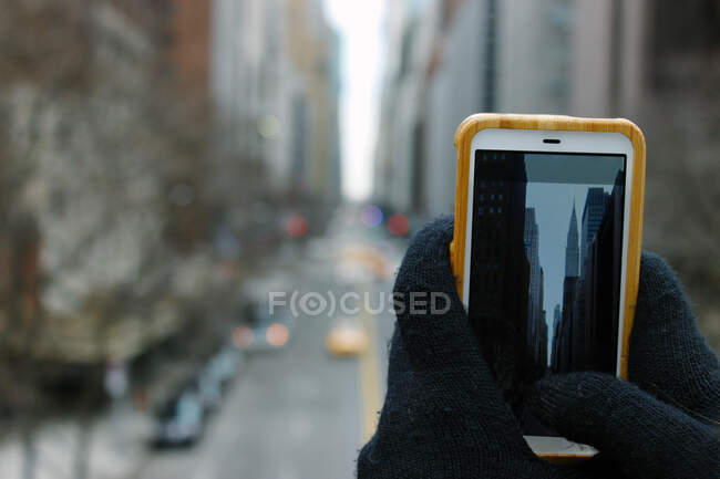 Tourist holding smartphone with both hands while taking cityscape of New York skyscrapers in winter time — Stock Photo