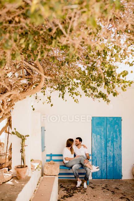 Uomo e donna sorridenti che si rilassano sulla panchina di legno in abbraccio al patio leggero in estate e si guardano — Foto stock