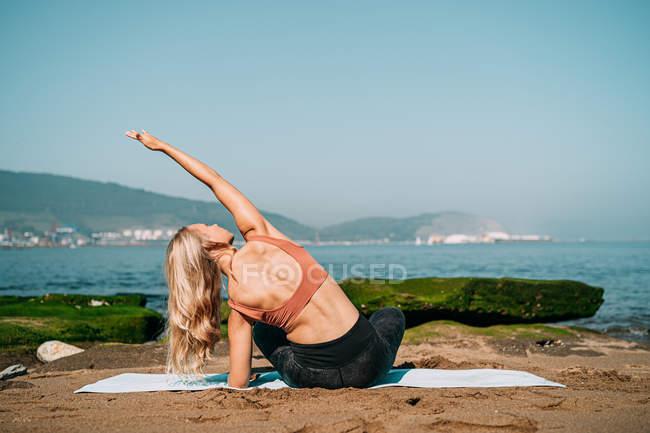 Friedliche Frau meditiert am malerischen Meeresufer — Stockfoto