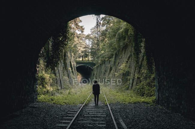 Anonymous woman standing in a abandoned aged railway — Stock Photo