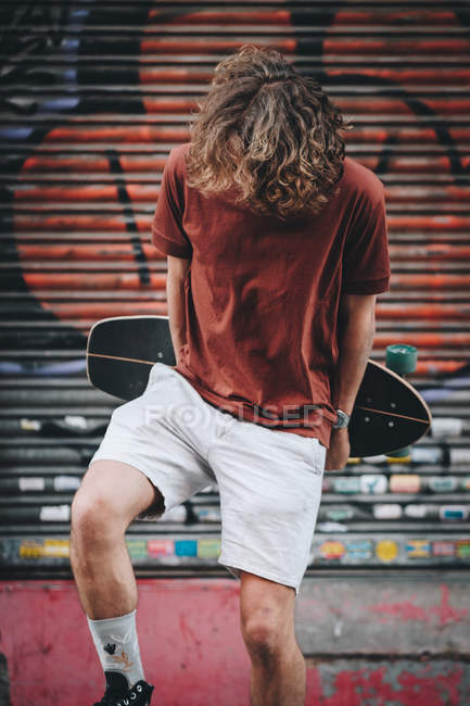 Confident man in casual clothes carrying longboard behind back while standing beside modern building - foto de stock