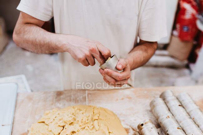 From anonymous confectioner putting fresh soft dough in small cup over table in bakery kitchen — Stock Photo