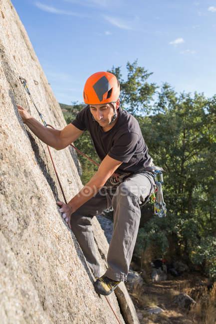 Man climbing a rock in nature with climbing equipment - foto de stock