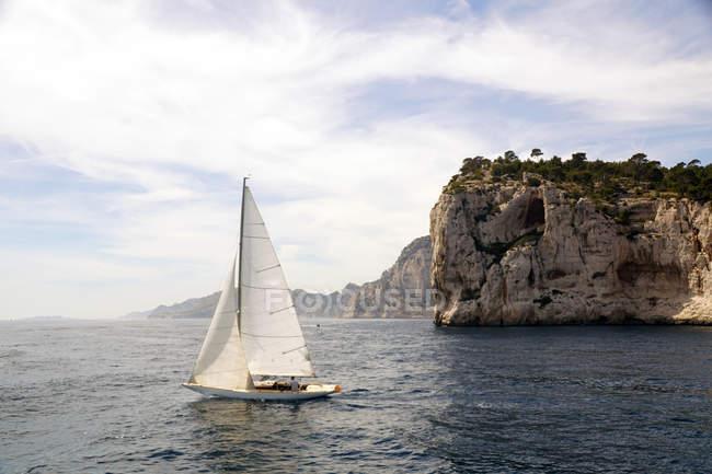Vue idyllique d'un voilier blanc avec une personne sans visage ciel nuageux et falaises du massif de Calanques en Europe France — Photo de stock
