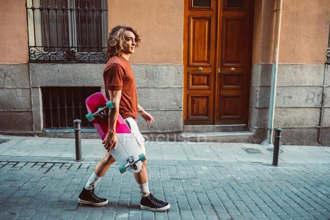 Vista lateral del encantador deportista que sostiene longboard mientras camina por la calle de verano de la ciudad. - foto de stock