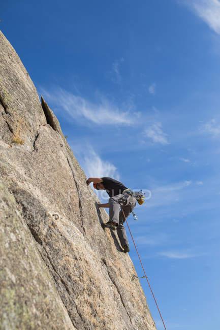 De baixo do homem escalando uma rocha na natureza com equipamento de escalada — Fotografia de Stock