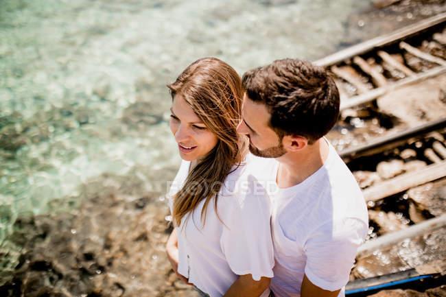 Glückliche Liebhaber kuscheln an Bucht — Stockfoto