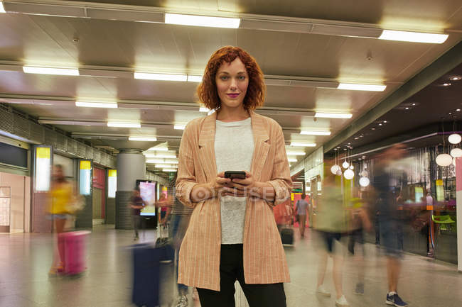 Red haired young woman using smartphone at station — Stock Photo