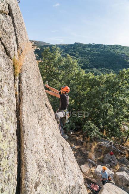 Hombre escalando una roca en la naturaleza con equipo de escalada - foto de stock