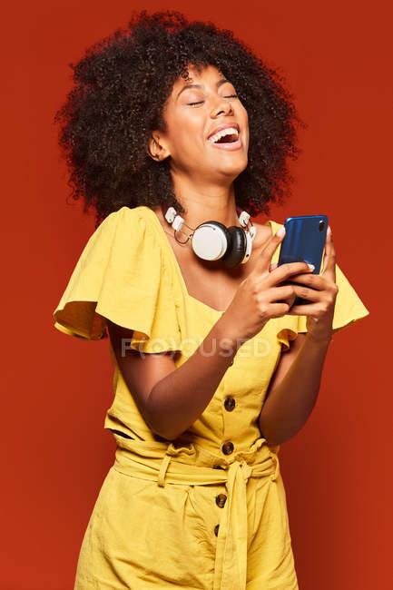 Африканка - американка, яка носить навушники на шиї, користується мобільним телефоном і голосно сміється на яскравому червоному фоні. — стокове фото