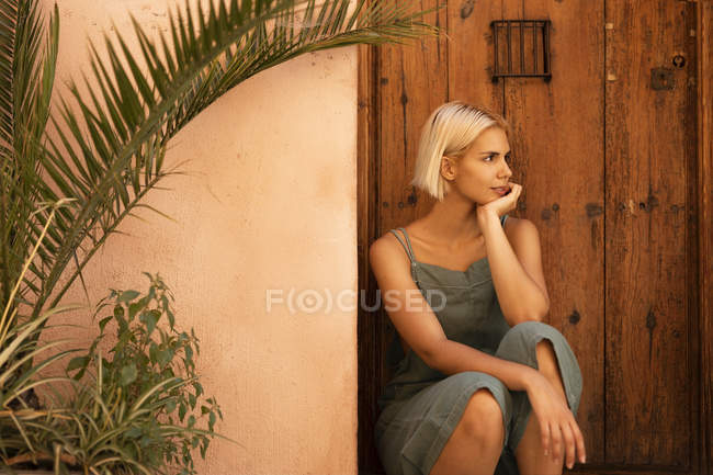 Young woman looking away while sitting near wooden door and plants in yard — Stock Photo