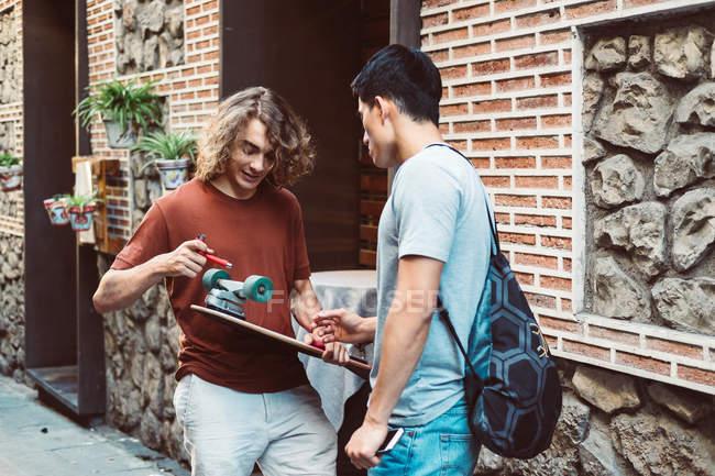 Внимательные мужчины в повседневной одежде разговаривают и держат лонгборд, стоя у городского здания — стоковое фото