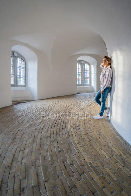 Casual woman leaning on wall in spacious gallery with windows — Stock Photo