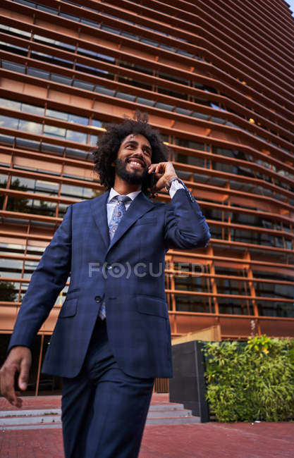 From below view of happy african american male entrepreneur in formal wear having conversation on mobile phone — Stock Photo