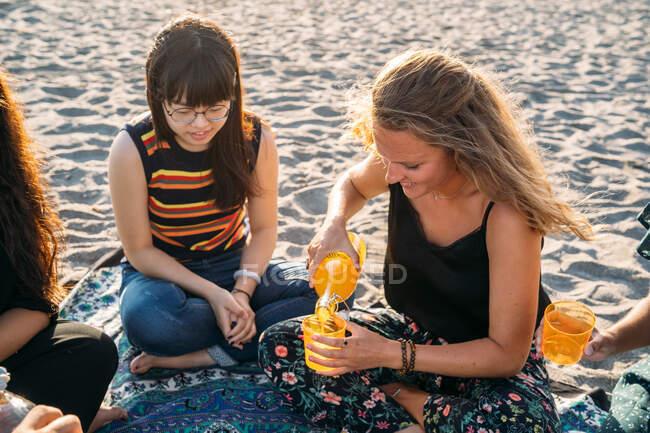 Uma linda garota loira derramando suco de laranja em um copo com seu amigo asiático na praia — Fotografia de Stock