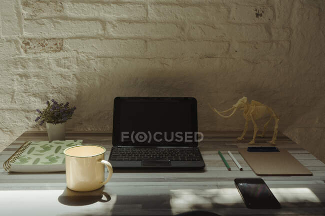 Large metal cup placed on desk near modern devices and various stationery against brick wall at home — Stock Photo